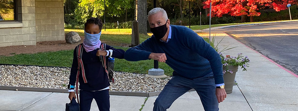 Interim Head of School Mark Brooks greets a lower school student with an elbow bump.