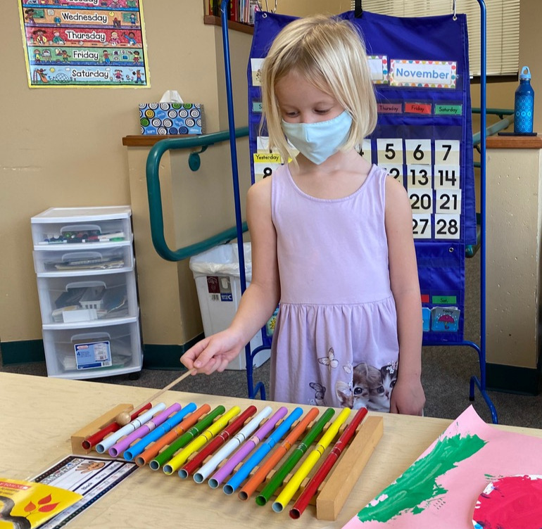 An in-person Pre-Kindergarten student practices a mini xylophone.